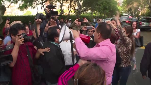 stockvideo's en b-roll-footage met people gather outside the uruguayan ambassador's residence in lima after former peruvian president alan garcia requested asylum in the embassy with... - former
