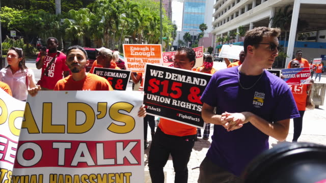 people gather together to ask the mcdonald's corporation to raise workers wages to a $15 minimum wage as well as demanding the right to a union on... - mcdonald's stock videos and b-roll footage