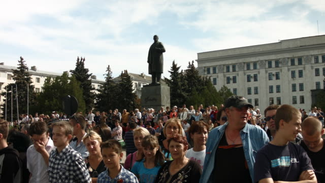 ws people gather under a statue of lenin as they await a military rally ukraine lugansk a separatist held city close to the border with russia has... - ukraine stock-videos und b-roll-filmmaterial