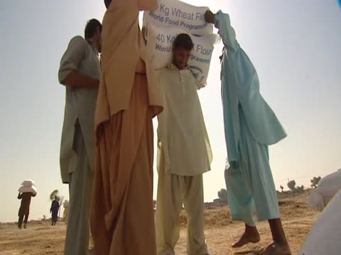 people gather up bags of rice during the first round of food aid distribution following devastating pakistan floods - ausgemergelt stock-videos und b-roll-filmmaterial