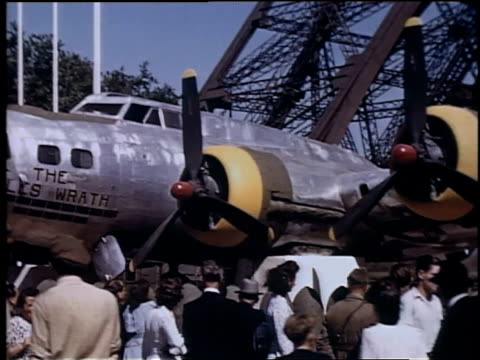 people gathered around airplane at the base of the eiffel tower / paris, france - besichtigung stock-videos und b-roll-filmmaterial