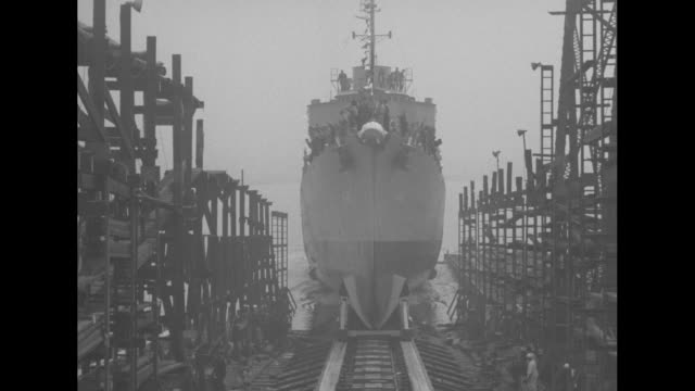 people gathered at bow of uss fletcher before launch / destroyer moving backwards on tracks christening group waving scaffolding on sides / mrs edith... - skeppsbyggare bildbanksvideor och videomaterial från bakom kulisserna