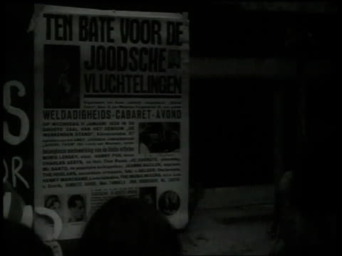 stockvideo's en b-roll-footage met 1938 montage people gathered in front of window reading poster news / amsterdam, netherlands - 1938