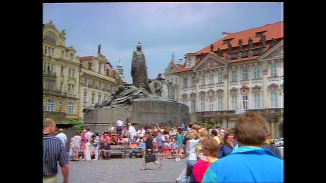 people gathered in old town square on a sunny day horse carriages pass by the frame people walking by outdoor stalls selling dolls and crafts statue... - prague old town square stock videos & royalty-free footage