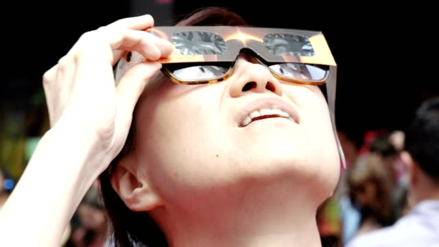 stockvideo's en b-roll-footage met people gathered in times square to watch the solar eclipse broadway and 7th avenue midtown manhattan new york city usa - de ruimte en astronomie