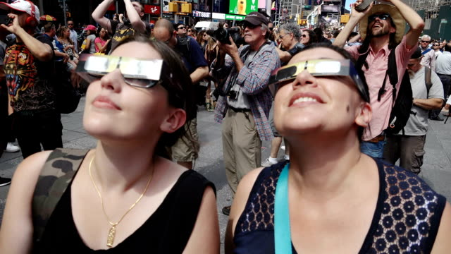 people gathered in times square to watch the solar eclipse. broadway and 7th avenue, midtown manhattan, new york city, usa. - sunglasses stock videos & royalty-free footage