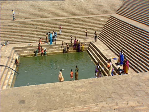 people gathered round pool of water at foot of steps to temple, india - number of people stock videos & royalty-free footage