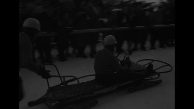 people gathered with bobsleds at start of course / sled under start banner / riding downhill at start of race / man of twoman team pushes sled / four... - bobsleighing stock videos & royalty-free footage