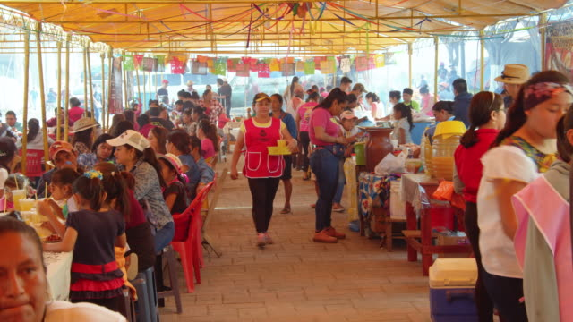 people gathering under a decorated tent and eating street food during the zoque coiteco festival in chiapas, mexico - traditional festival stock videos & royalty-free footage