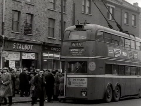 People get off a double decker bus on a busy street
