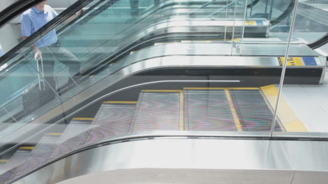 ms people getting off escalator at airport / chicago, illinois, united states - flugpassagier stock-videos und b-roll-filmmaterial