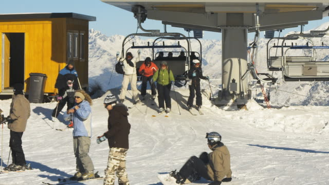 ws people getting off form chairlift / queenstown, new zealand - seggiovia video stock e b–roll
