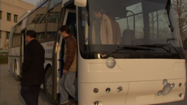 MS PAN People getting off Qinqua University fuel cell bus, an official opening up compartment to show fuel cells, Beijing, China