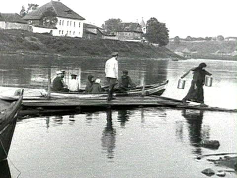 ws people getting off small boat after crossing river man getting in audio/ russia - 1918年点の映像素材/bロール
