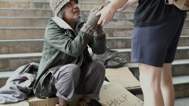 people give food to homeless on the footpath. - homelessness stock videos & royalty-free footage
