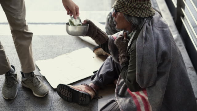people give money to homeless begging bowl on the footpath. - begging social issue stock videos and b-roll footage