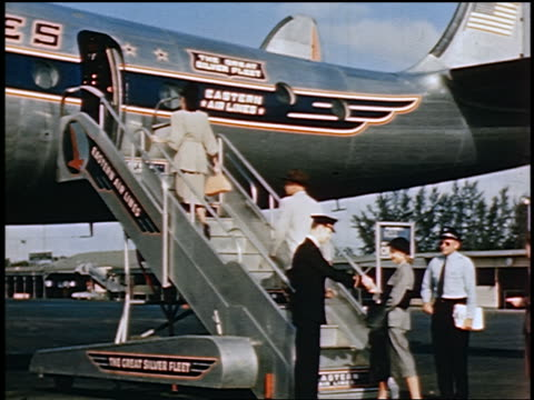 1950 people giving tickets to ticket agent walk up stairs to board Eastern Airlines Constellation