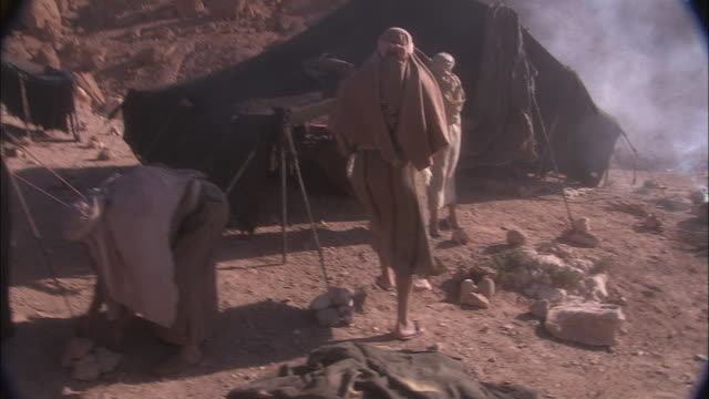 people go about their daily lives in a desert camp in morocco. - minority groups stock videos & royalty-free footage