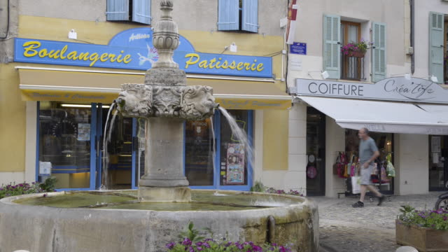 people go in a bakery on marketplace with fountain in valensole - french bakery stock videos & royalty-free footage