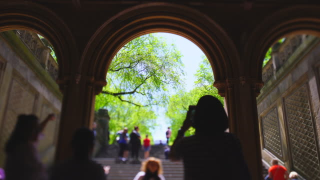 vídeos de stock e filmes b-roll de people go through under the bethesda terrace walkway, and walk up the stairs to the mall in central park at new york city ny usa on may 06 2019. - fonte bethesda
