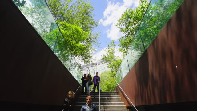 People go up and down the stairs of High Line Park at Whitney Museum Entrance on May. 08 2017. Fresh green trees are growing in spring and surround the High Line Park in New York.