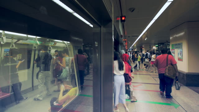 vidéos et rushes de tl ws people going in and out of a subway train. - singapour