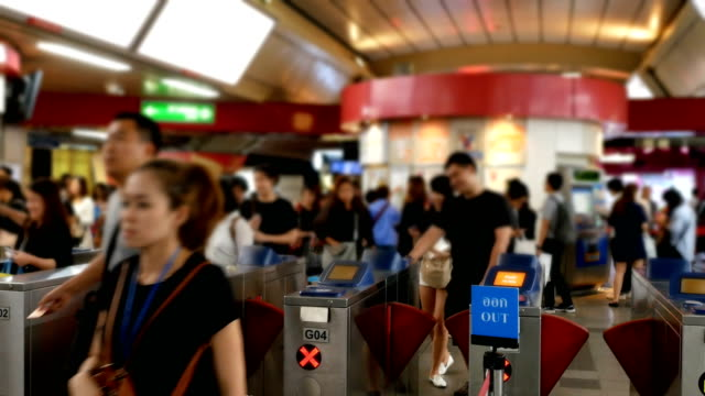 People going through the turnstile in the railway station