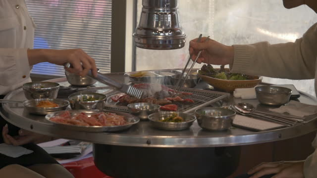 people grilling korean beef barbecue at a restaurant - 韓国文化点の映像素材/bロール