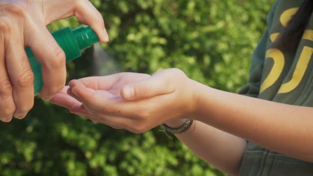 menschen handpflege im freien mit desinfektionsalkohol gel sauber waschen hand anti-virus-bakterien während der covid-19 krise - hygiene stock-videos und b-roll-filmmaterial