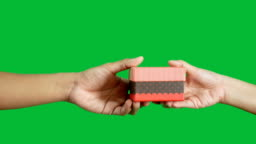 4K. people hand giving and take red gift box isolated on chroma key green screen background. season's greeting concept