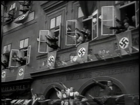 People hanging out windows and on rafters amid swastika flags to salute Hitler and his entourage / Sudetenland Czechoslovakia