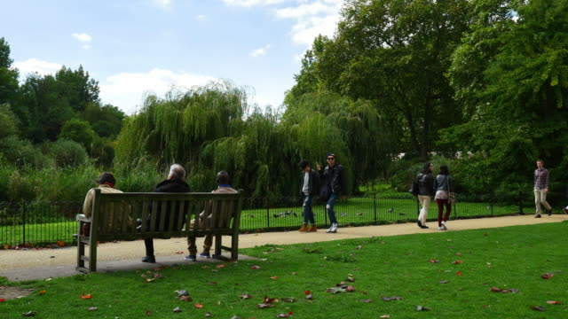 vidéos et rushes de people having a break in london st james's park - banc public