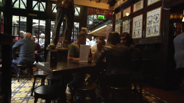 people having a drink in irish pub in dublin - pub stock videos & royalty-free footage