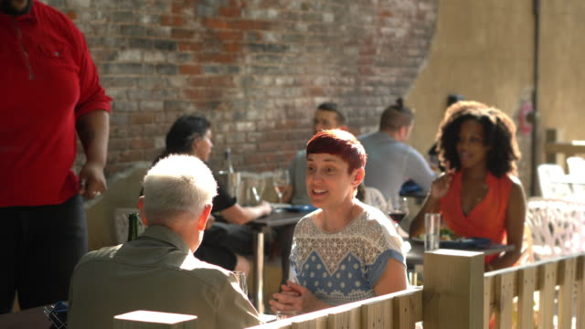 vidéos et rushes de people having a food and drinks at a outdoor sidewalk cafe. - terrasse