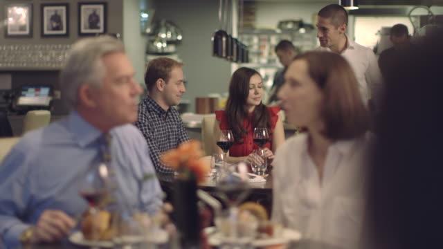 ms r/f people having food in restaurant, waiter serving food - テーブルマナー点の映像素材/bロール