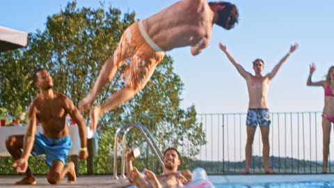 slo mo ds persone che si divertono a una festa in piscina al tramonto mentre fanno il tifo per il loro amico facendo un salto in acqua - swimming pool video stock e b–roll