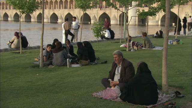 MS People having picnic on lawn, Si-o-Se Pol Bridge (Allah-Verdi Khan Bridge) in background, Isfahan, Iran