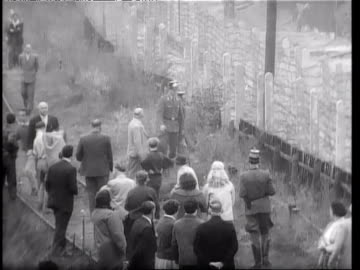 vidéos et rushes de people helping others escape through barbed wire fence of berlin wall, guards try to stop them / man escaping through barbed wire fence of berlin... - 1961