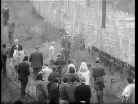 vídeos de stock e filmes b-roll de people helping others escape through barbed wire fence of berlin wall guards try to stop them / man escaping through barbed wire fence of berlin wall... - 1961