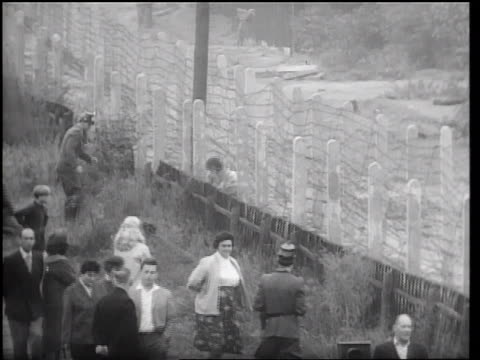 vídeos de stock e filmes b-roll de b/w 1961 people helping others escape thru barbed wire fence of berlin wall / germany / newsreel - 1961
