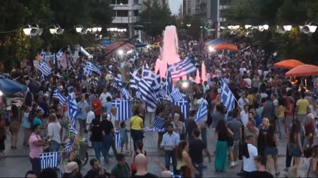 people hold a rally in front of the greek parliament in athens as 'no' vote ahead in greek referendum on july 5 2015 crowds are beginning to gather... - griechische flagge stock-videos und b-roll-filmmaterial