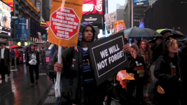 people hold banners and placards at a rally against police brutality in new york, united states on october 22, 2014. under the rainy skies of new... - theatre district stock videos & royalty-free footage