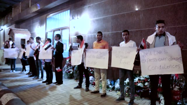 People hold placards during a gathering to commemorate the death of plane crash victims outside the Russian Embassy in Cairo Egypt Sunday Nov 1 2015