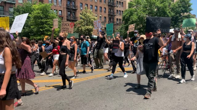 "people hold signs and chant ""george floyd, michael brown, shut the whole system down"" as they walk past a nypd vehicle during a rally in brooklyn to... - 1865 stock videos & royalty-free footage"