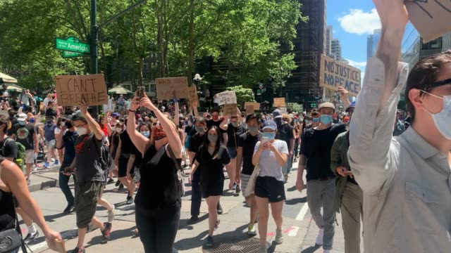 stockvideo's en b-roll-footage met people hold signs and chant no peace no justice as hundreds of protesters march in manhattan over the death on may 25 of a black man george floyd... - chanten