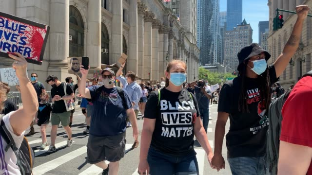 people hold signs as they march down the street during a rally in brooklyn to support the black lives matter movement and to commemorate the 155th... - 1865 stock videos & royalty-free footage