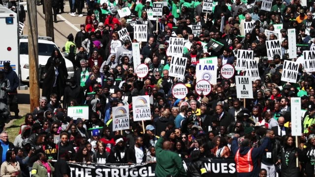 people hold signs as they participate in an event to mark the 50th anniversary of dr martin luther king jr's assassination april 4 2018 in memphis... - memphis tennessee stock-videos und b-roll-filmmaterial