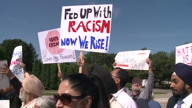 wgn people hold signs gathered in wheaton illinois in support of 53 yearold inderjit singh mukker a sikh man who was attacked a teenager from... - soziale gerechtigkeit stock-videos und b-roll-filmmaterial