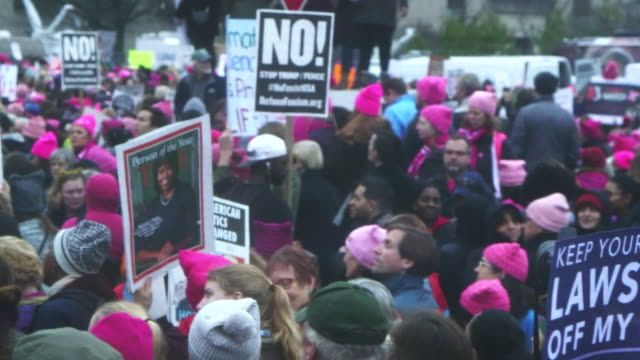 People hold up signs at Women's March in Washington DC