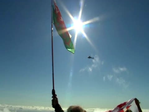 people hold welsh flags at the summit of mount snowton during the torch relay - flaming torch stock videos & royalty-free footage